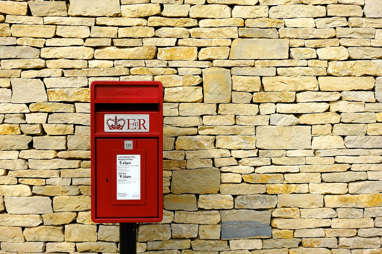 Red mailbox infront of a brick wall